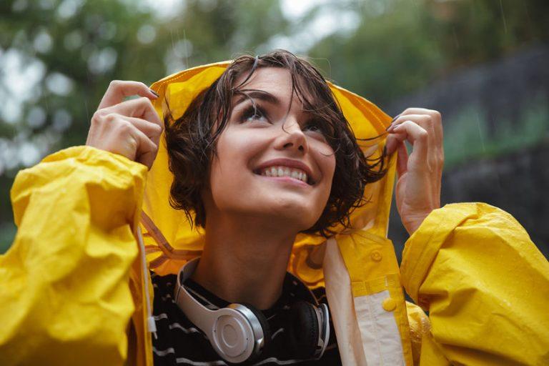 Mujer con auriculares inalambricos bajo la lluvia