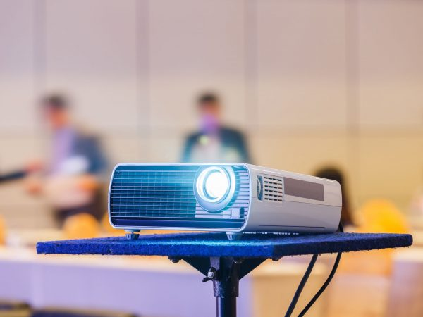 Close up projector in conference room with blurry people background