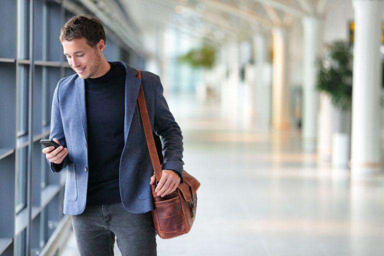 Un hombre andando mirando su móvil