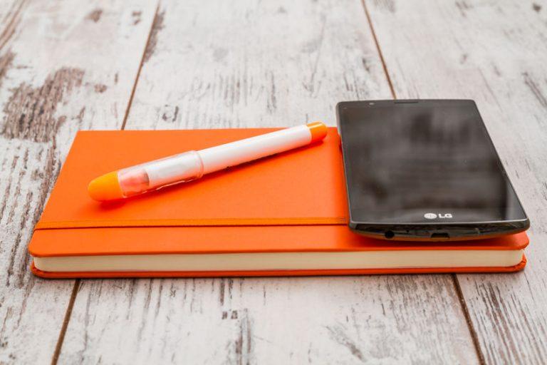 Un móvil encima de una agenda naranja en una mesa