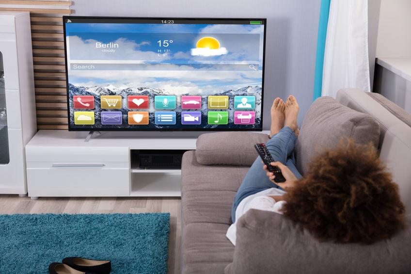 Mujer viendo televisión con coloridas aplicaciones en pantalla