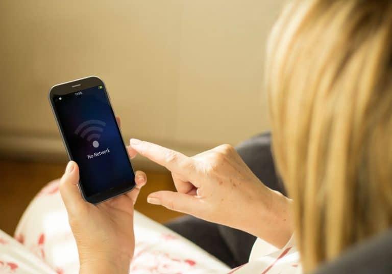 Una mujer conectado su móvil a u una red wifi