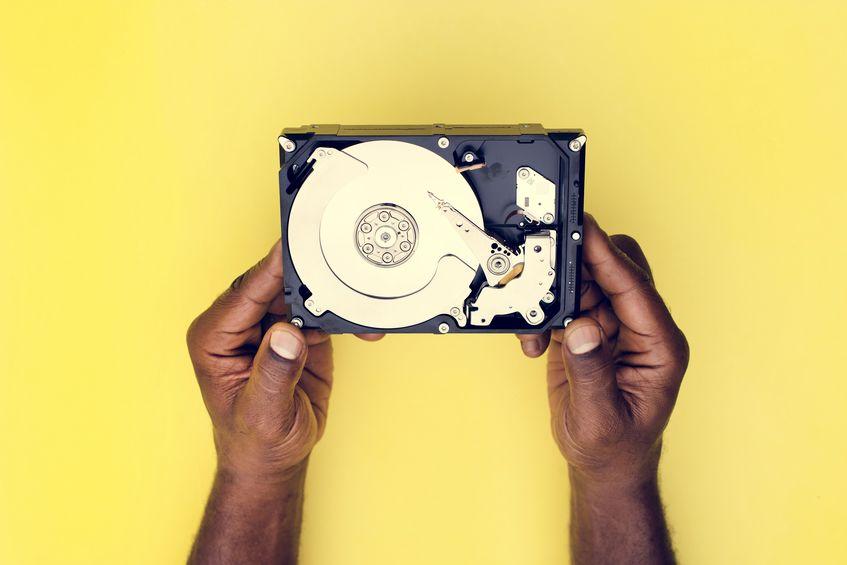 Manos sosteniendo disco duro en fondo amarillo