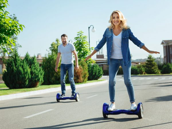 Satisfied with purchase. Joyful young husband and wife riding hoverboards and smiling happily, being pleased with their new purchase