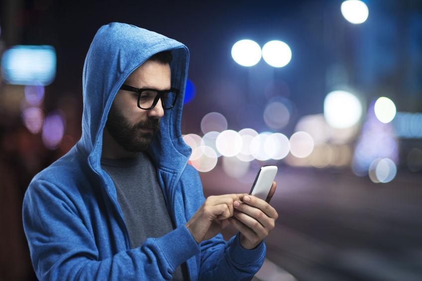 Hombre con capucha en la calle con smartphone