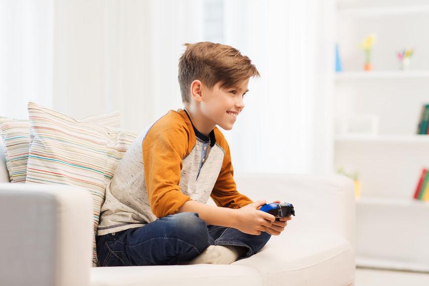 Niño en sofá jugado con joystick
