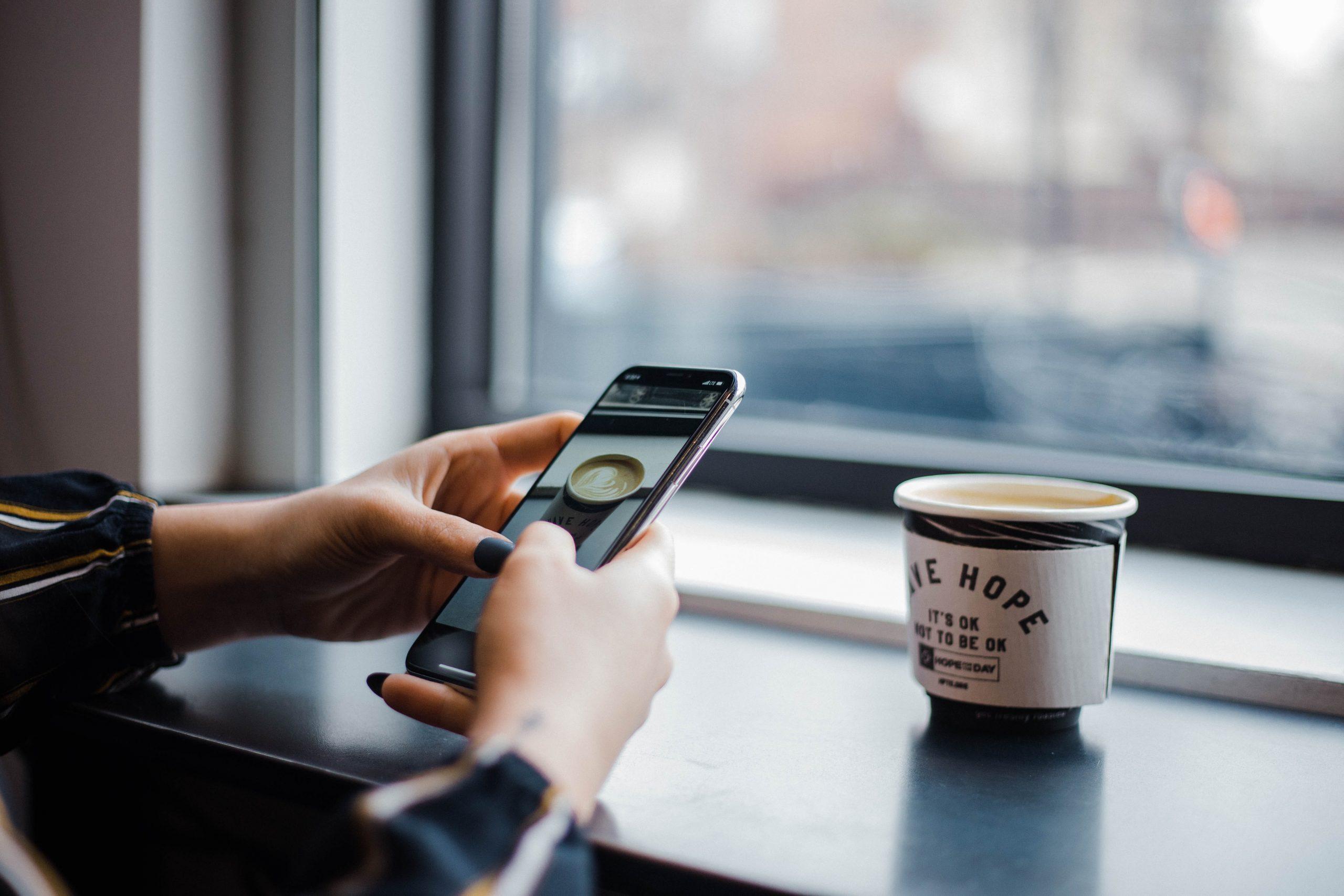 Mujer usando smartphone Huawei en mesa junto a ventana con taza de café
