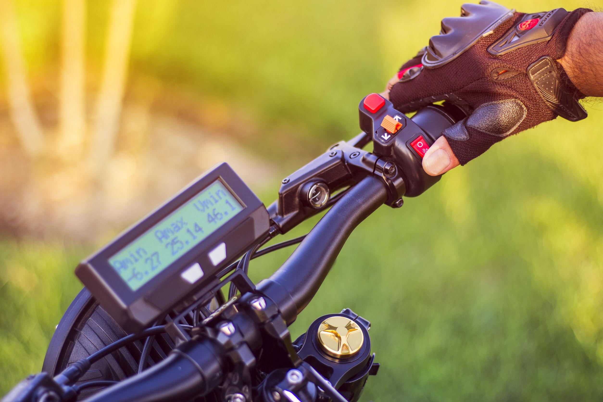 Mano de hombre haciendo clic en el botón de control señal de parada trasera de la bicicleta eléctrica.