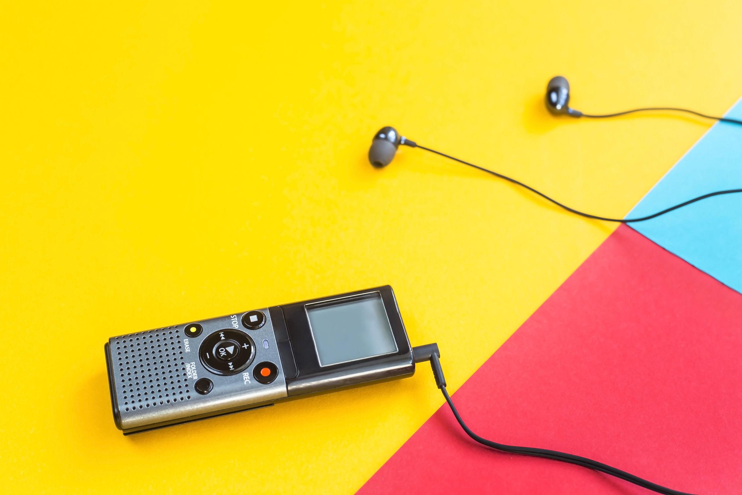 Grabadora de voz negra con auriculares en un fondo combinado amarillo, azul y rojo
