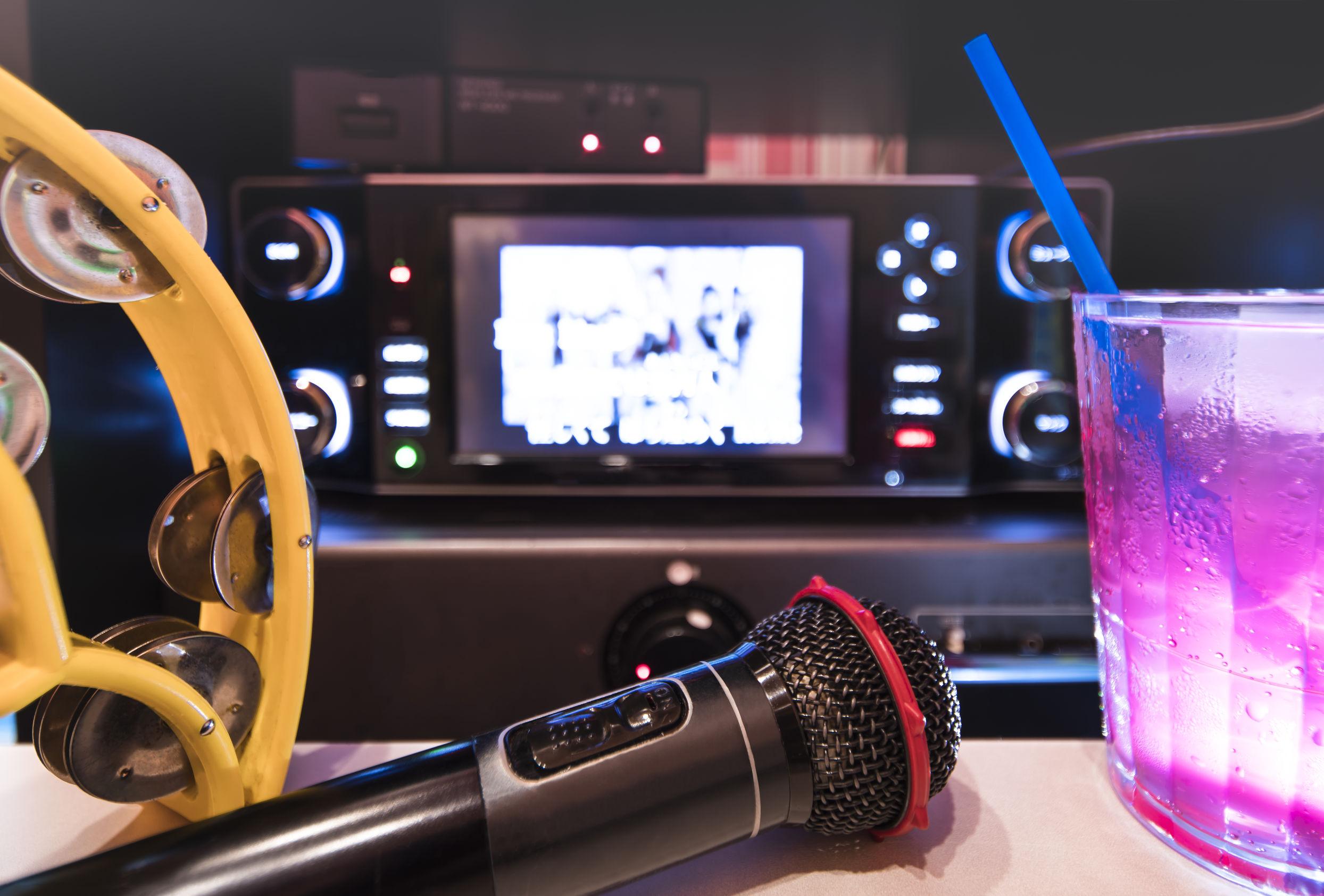 Micrófono negro en club de karaoke, con mando a distancia, refrescos de melón y fresa, pandereta amarilla y pantalla para cantar música en la fiesta del escenario.