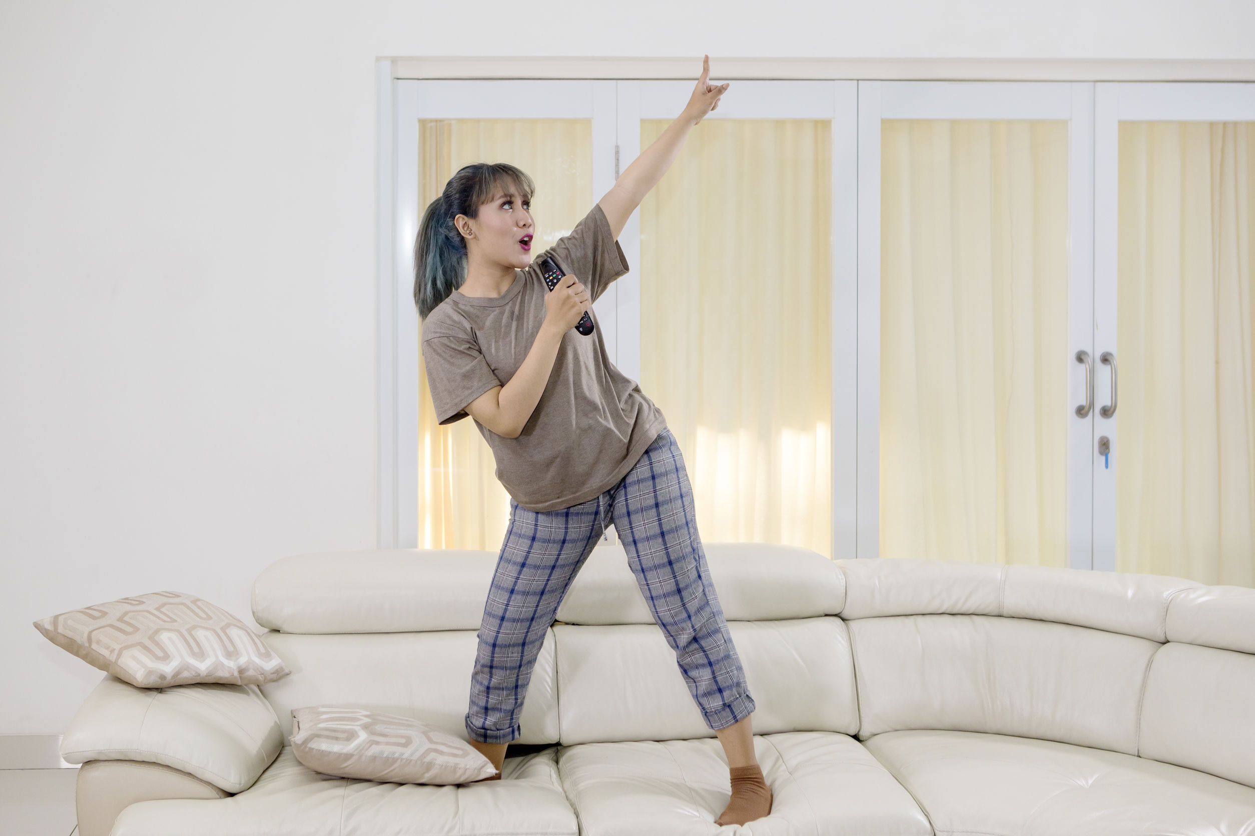 Mujer joven canta y baila en el sofá