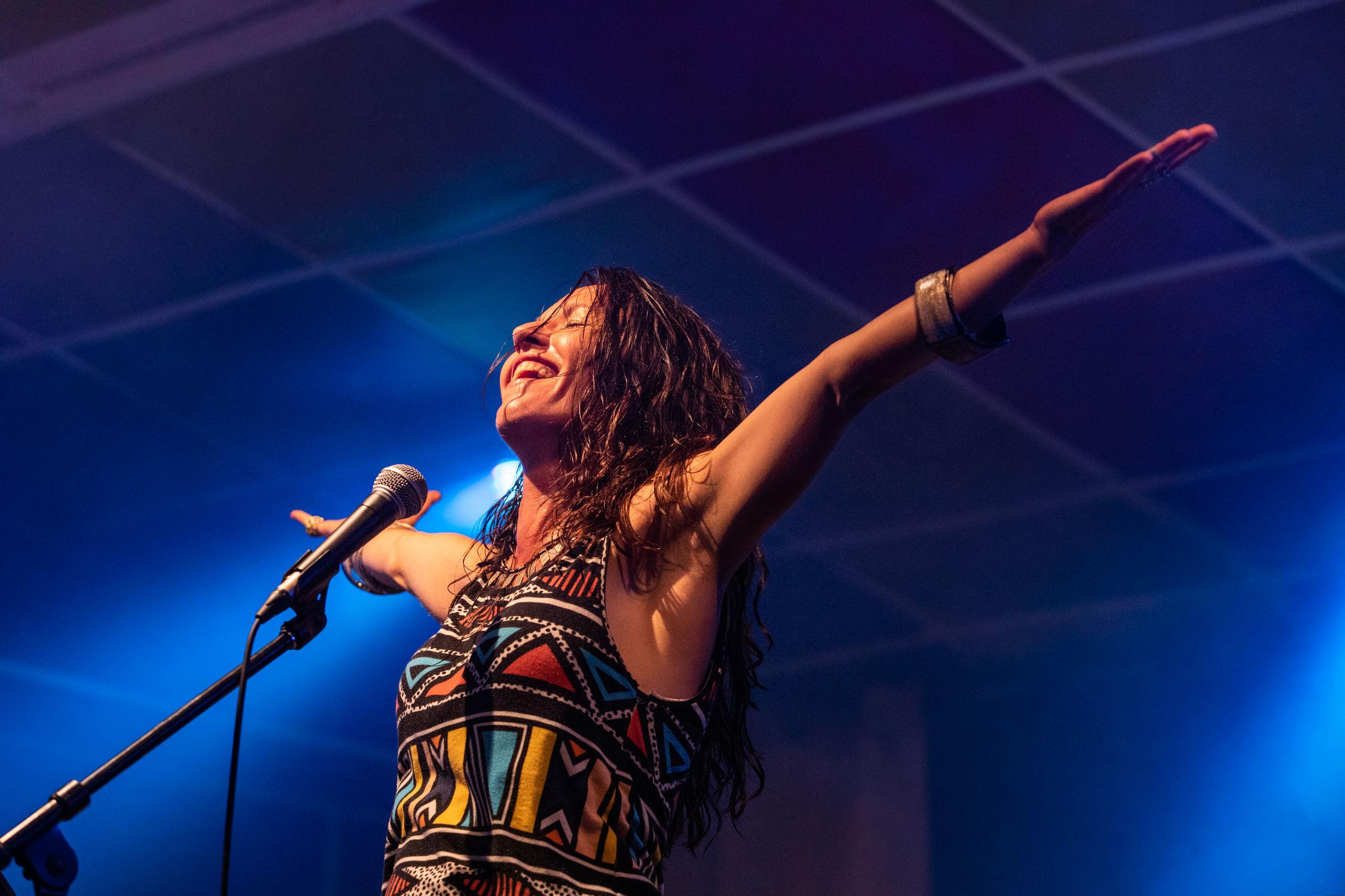 Una mujer músico es vista desde un ángulo bajo mientras canta y sonríe con la audiencia con las manos levantadas durante una actuación