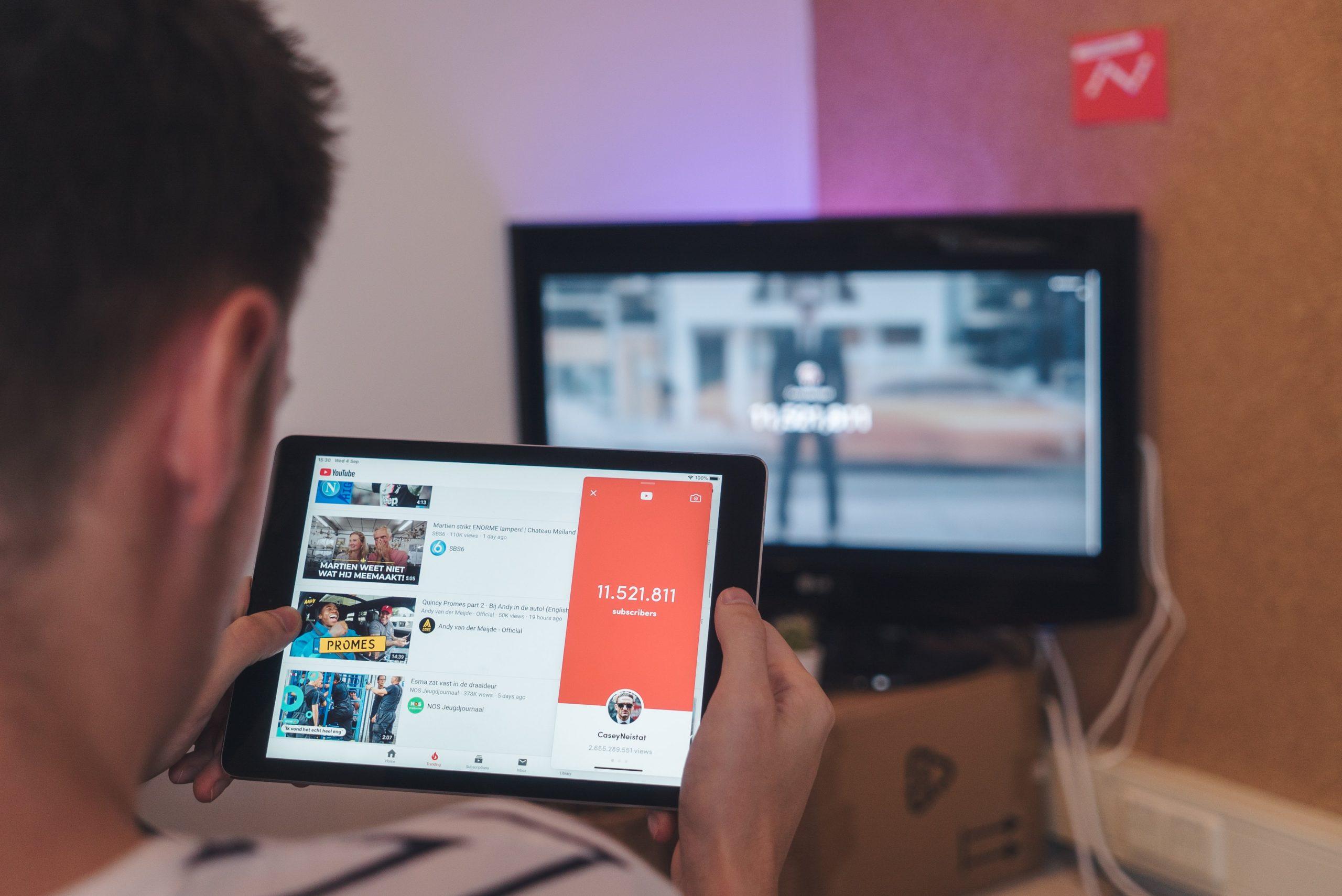 Hombre sentado frente a TV sosteniendo una tablet