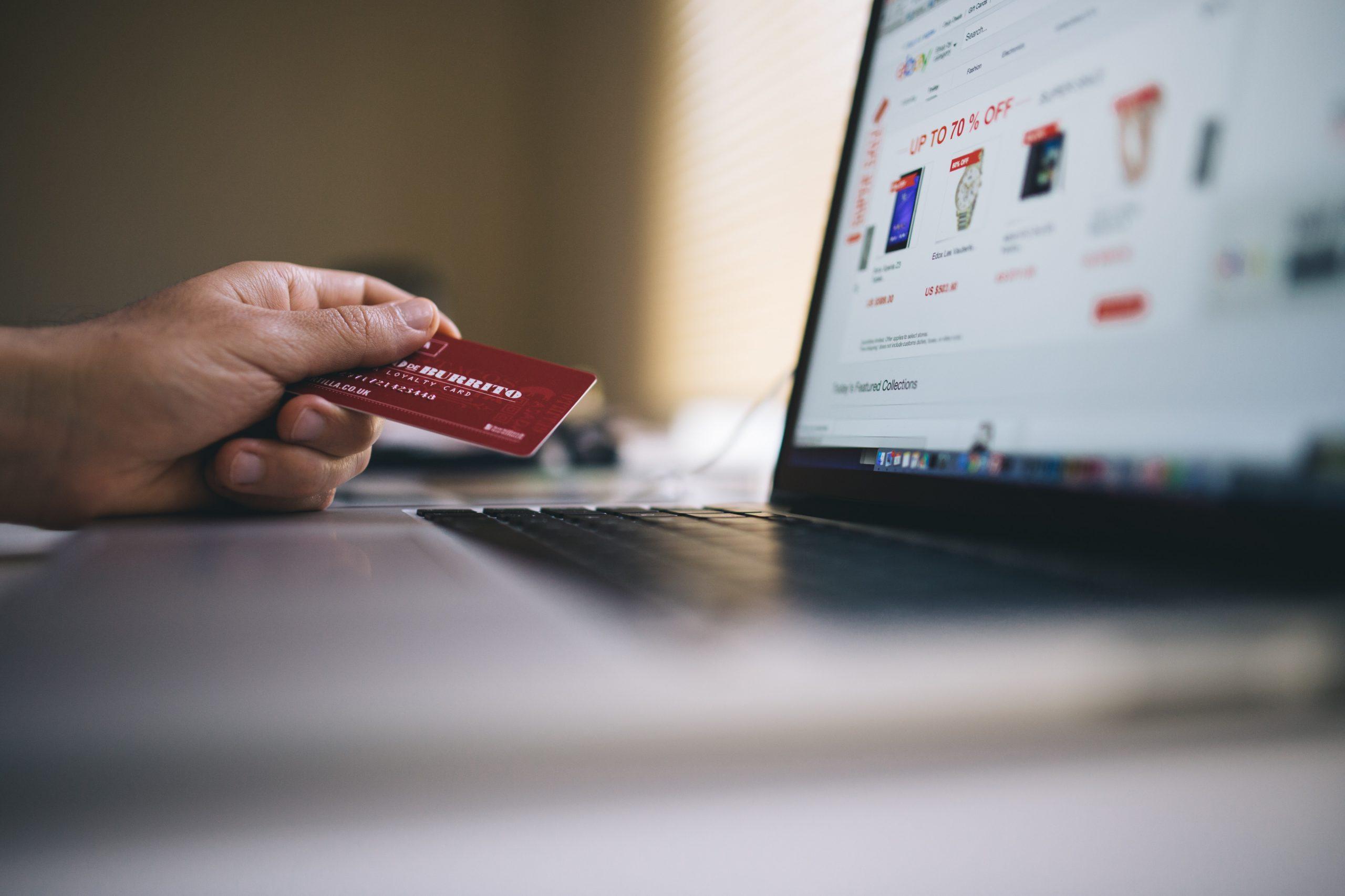 Imagen de una mano sostenierndo una tarjeta frente a una laptop