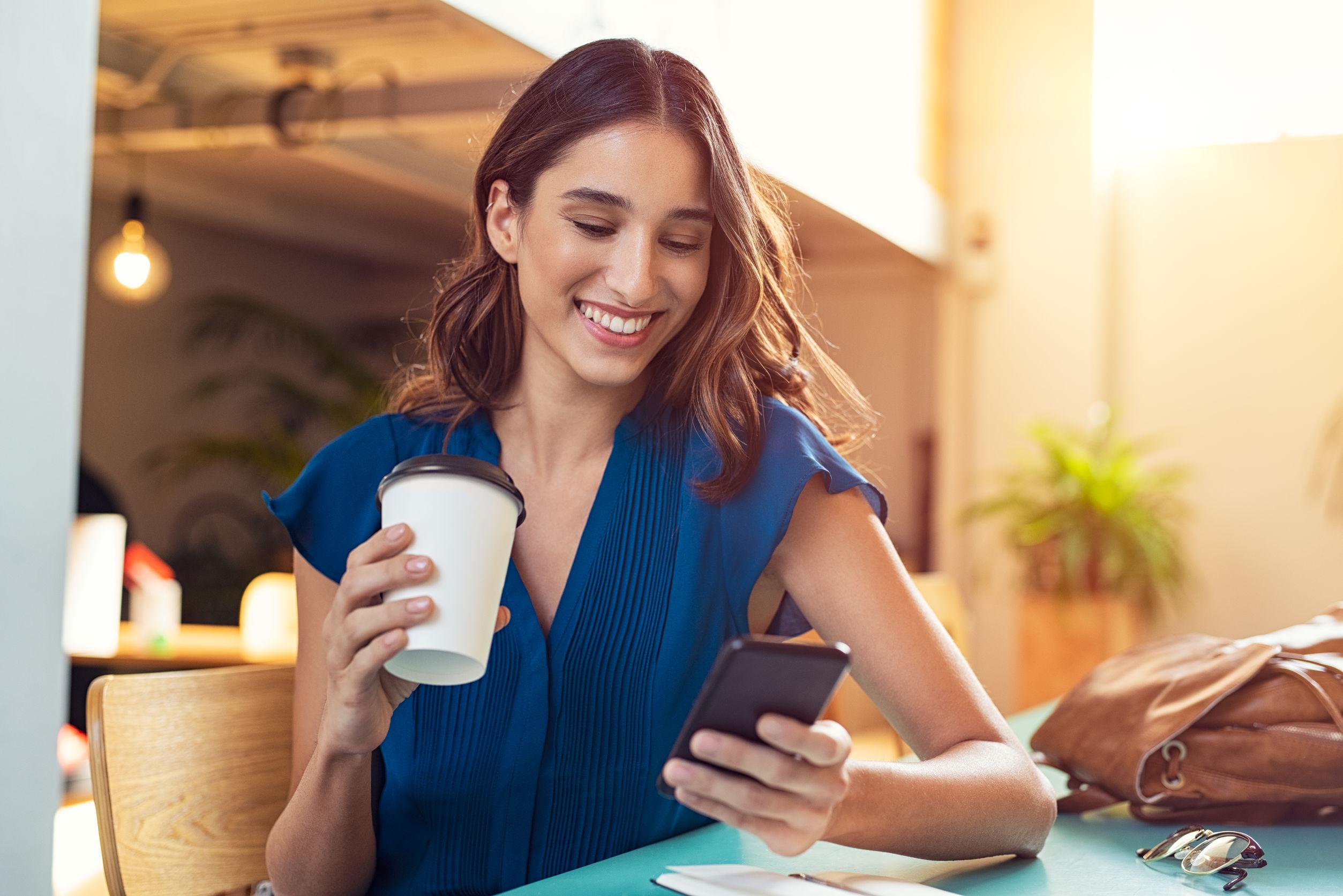 Mujer tomando cafe sosteniendo un smartphone en su mano