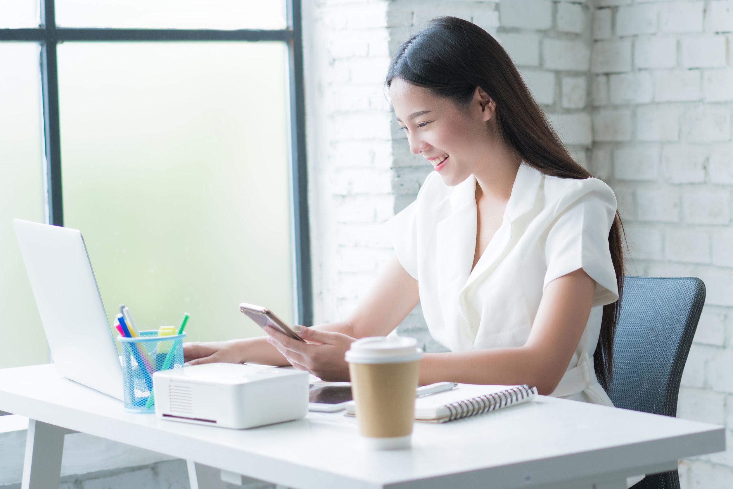 Mujere asiática trabajan ahora en el escritorio de su casa es feliz.