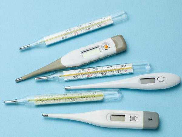 Medical thermometers glass and electronic on blue background.