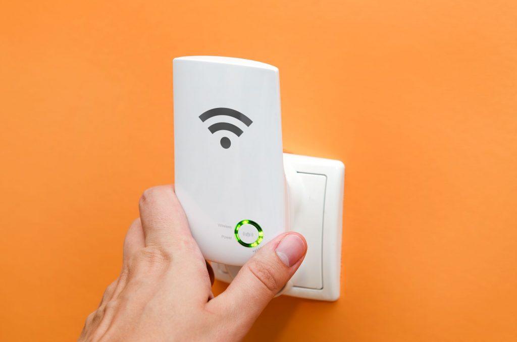 Repetidor WiFi en toma de corriente en pared naranja.