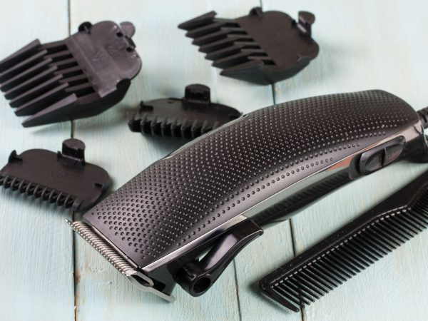 hair trimmer with a comb on the wooden background.