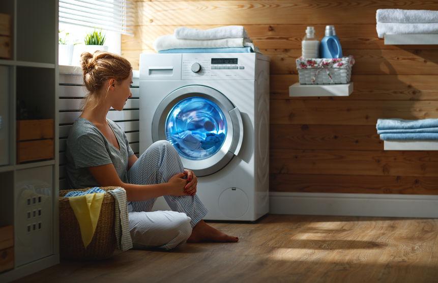 chica sentada al lado de la lavadora