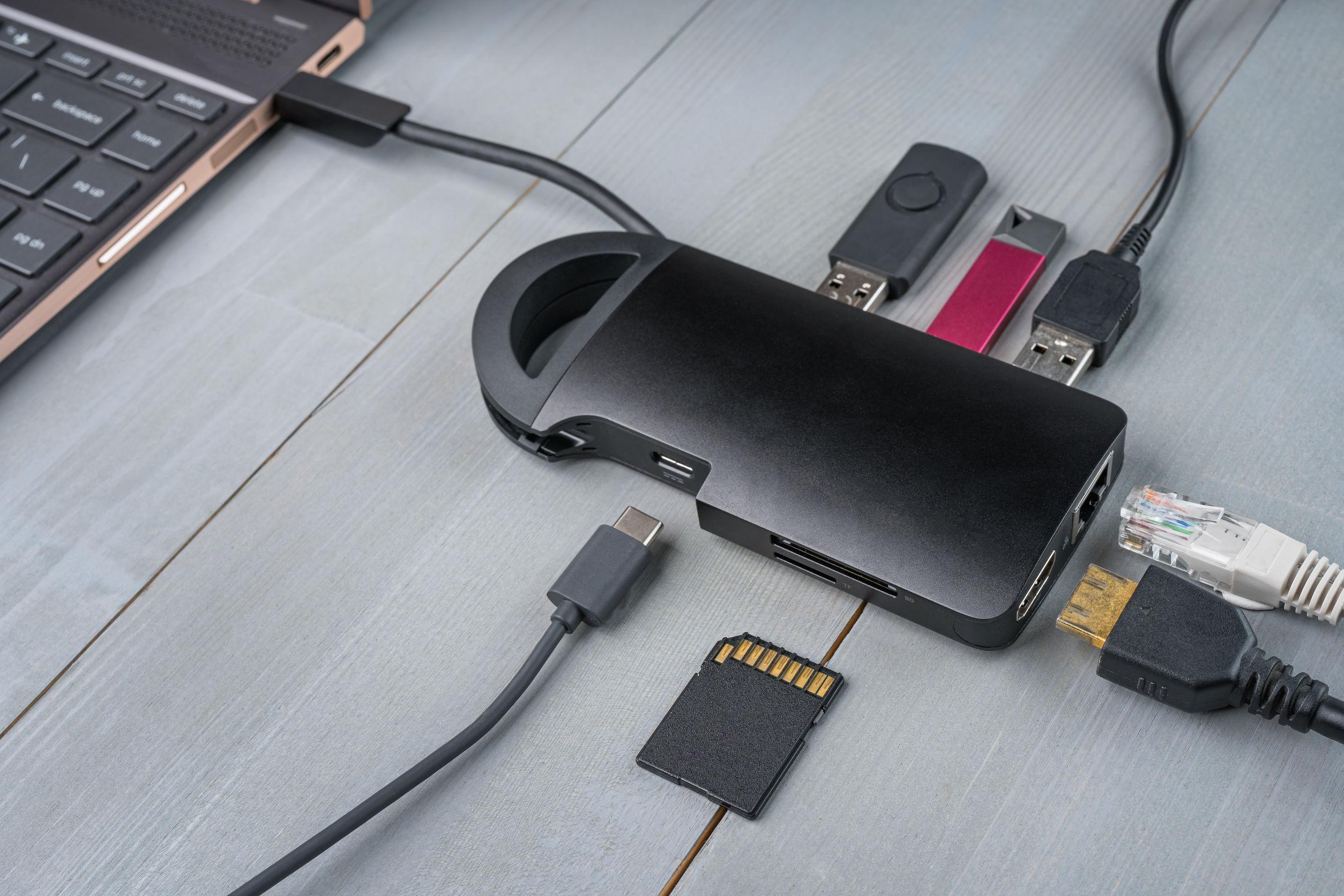 Adaptador o concentrador USB tipo C conectado a la computadora portátil con varios accesorios: pendrives, hdmi, ethernet, tarjeta de memoria, cables.
