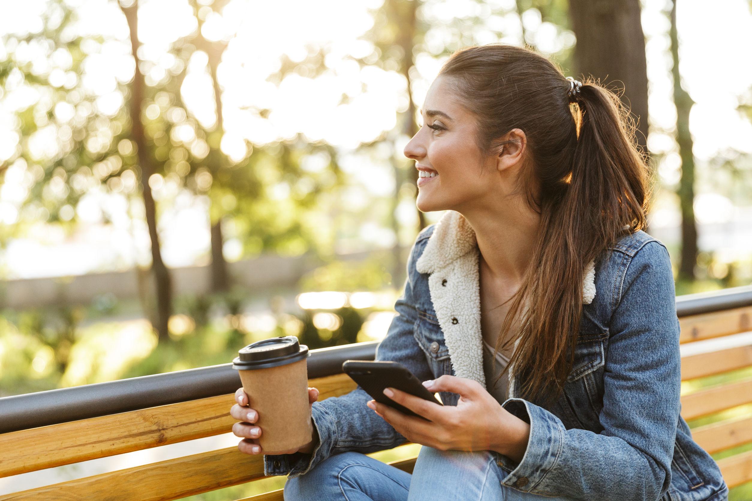 Mujer sonriente vistiendo chaqueta sentado en un banco en el parque sosteniendo un teléfono móvil, bebiendo café