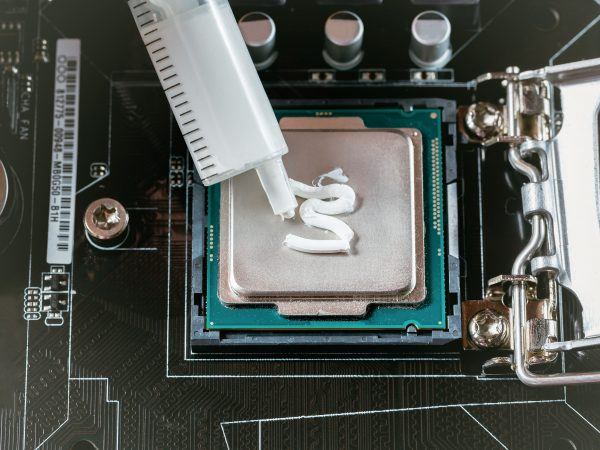 Applying thermal paste during CPU installation close up in the motherboard.