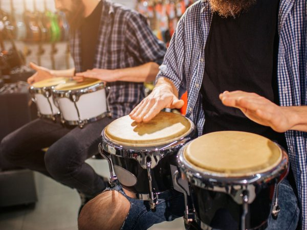 Two guys having beat on african drums. They sit and play together on instruments