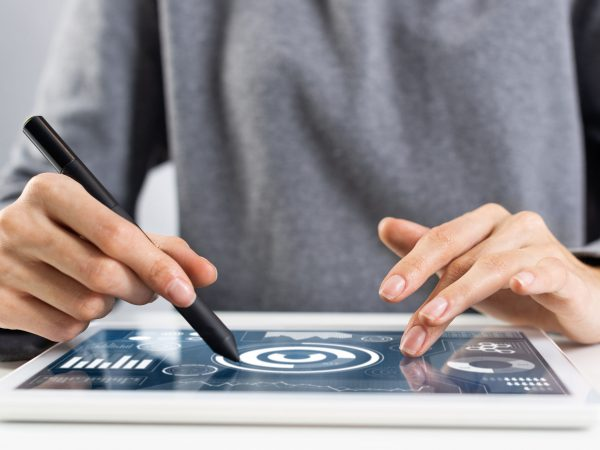 Woman using tablet computer for project management. Close-up of female hand holding pen and touching screen of tablet device. Online stock trading and investing. Mobile smart device in business