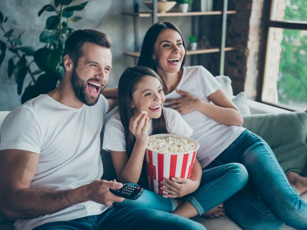 Portrait of nice attractive lovely positive glad cheerful cheery family wearing, casual white t-shirts jeans denim sitting on sofa having fun watching funny video enjoying spending free time