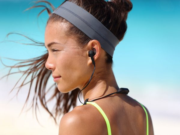 53759189 – fitness girl with sport in-ear wireless headphones. asian female athlete woman runner wearing bluetooth earphones with wing tip design for sports activities. portrait closeup.