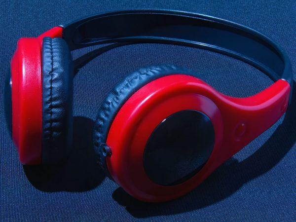 Red headphones on a dark background. Audio headphones on the table. Dark red headphones background.