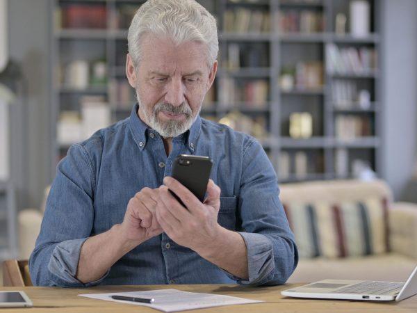 Focused Senior Old Man using Smartphone in Modern Office