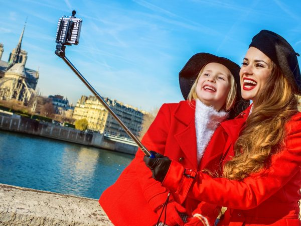 Bright in Paris. modern mother and child tourists in red coats on embankment in Paris, France taking selfie using selfie stick