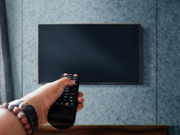 Watching Television Concept. Hand holding TV's Remote to Control or Changing Channel. Relaxation in Modern Living Room. Focus on Remote