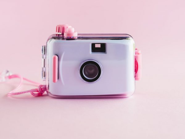 Camera waterproof toy on pink background with copy space