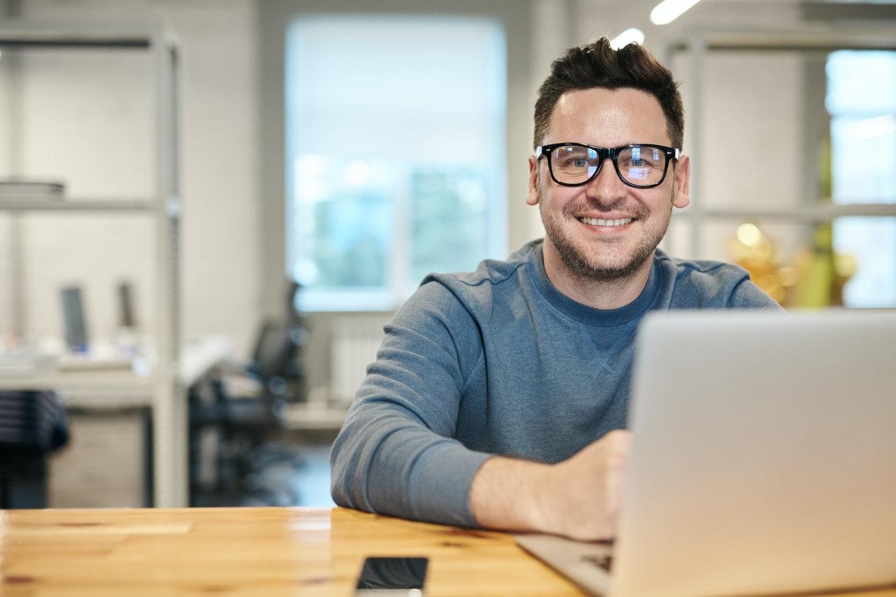 Hombre sonriente con gafas para ordenador