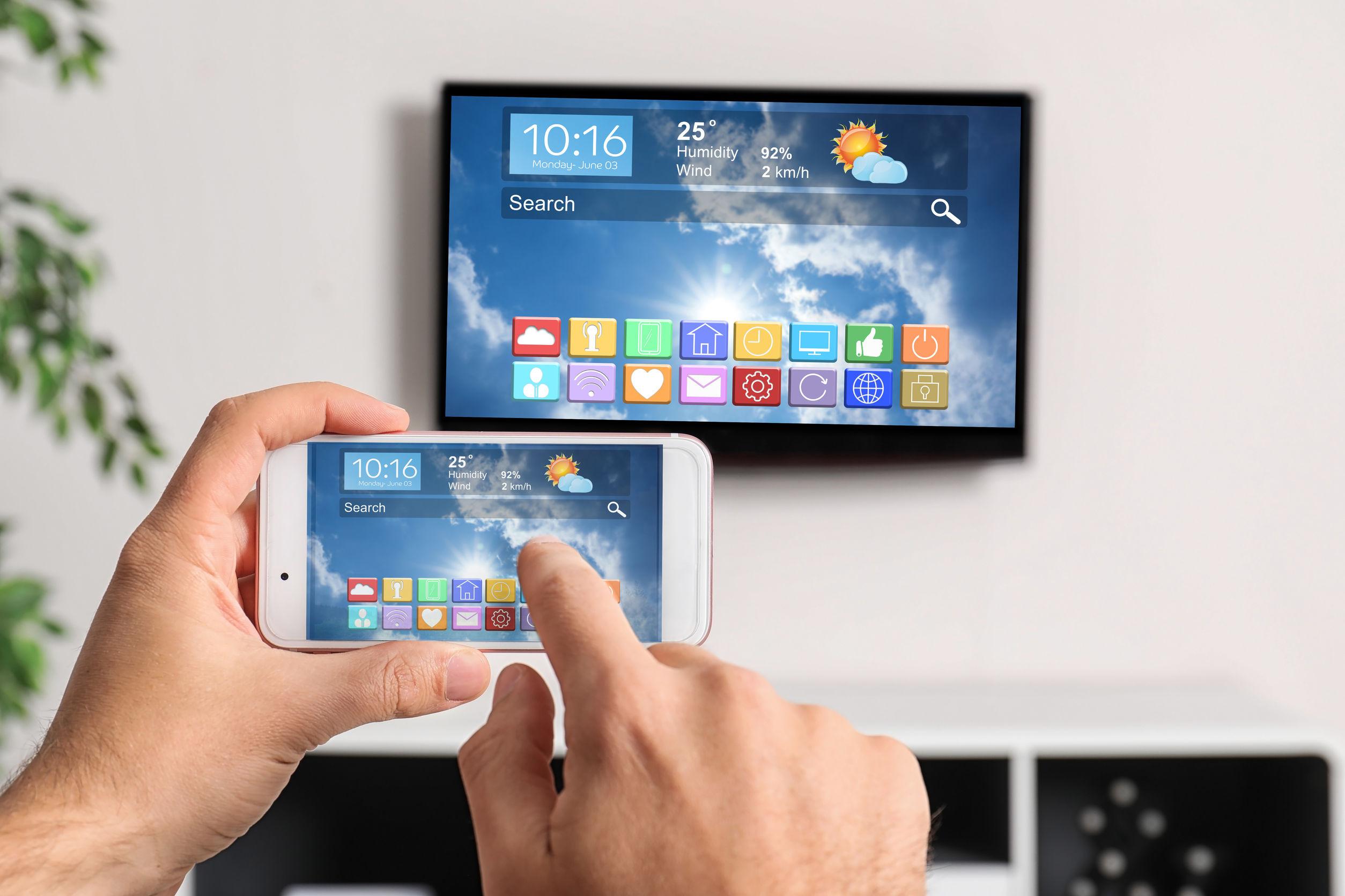 Hombre usando el teléfono conectado a la televisión inteligente en el salón