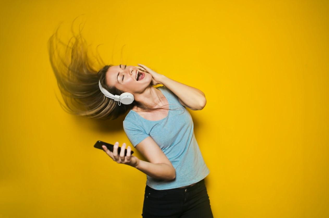 Mujer feliz escuchando musica con auriculares