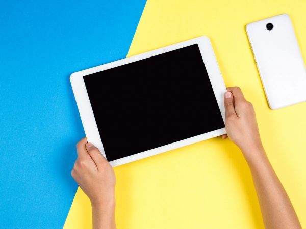 Kid hands holding tablet computer on blue and yellow background.
