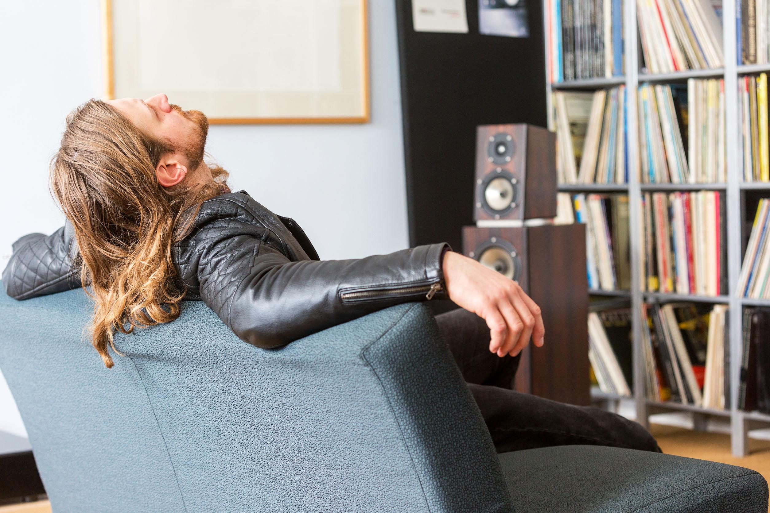 Un audiófilo recostado en un sofá escuchando música