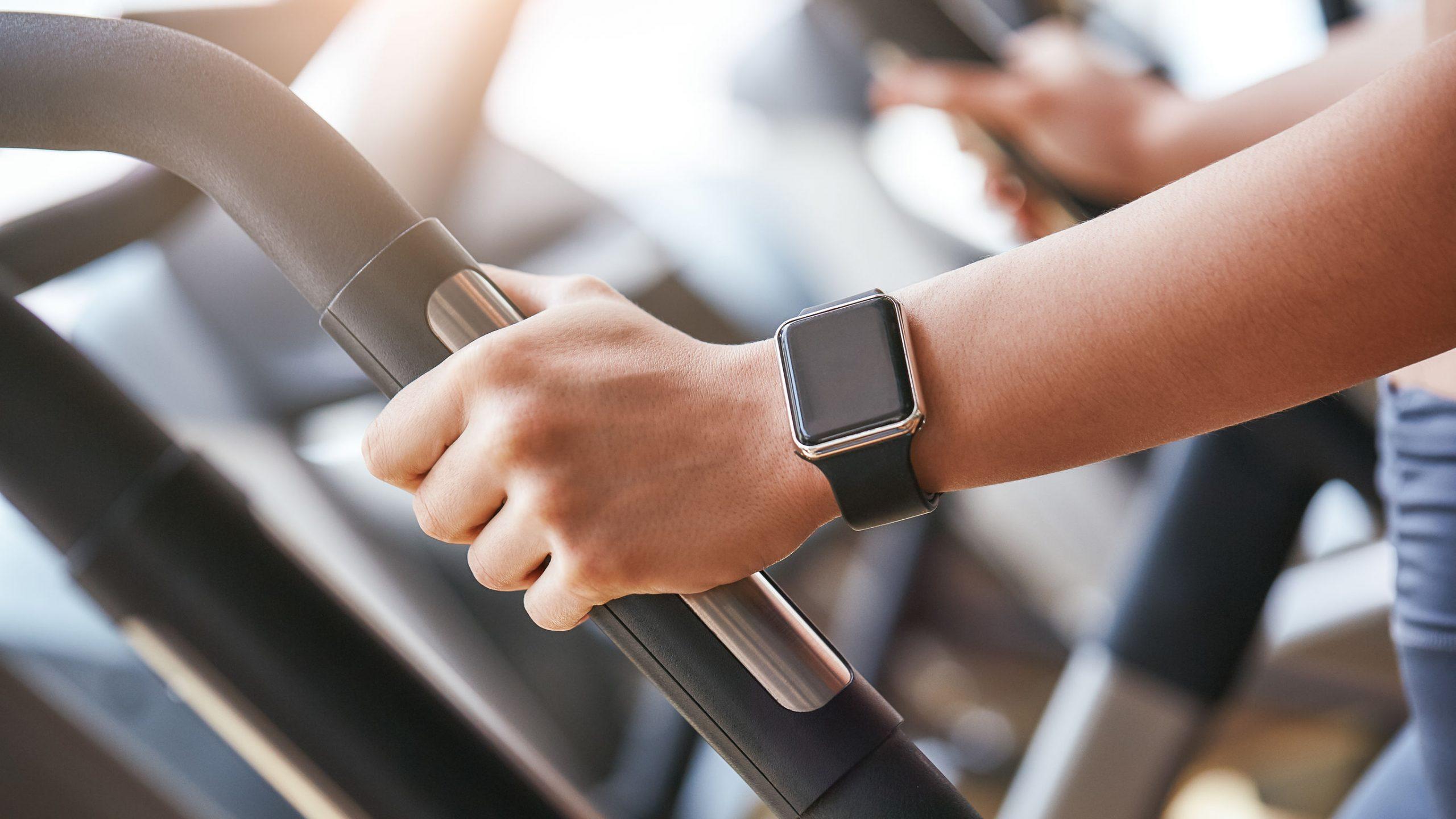 Foto de primer plano de reloj inteligente en la mano de la mujer sosteniendo el mango de la máquina de cardio en el gimnasio