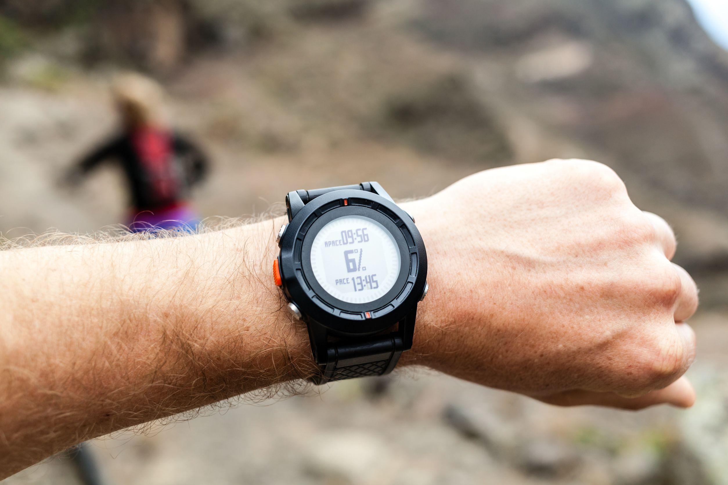 Corredor en el camino de la montaña mirando smartwatch