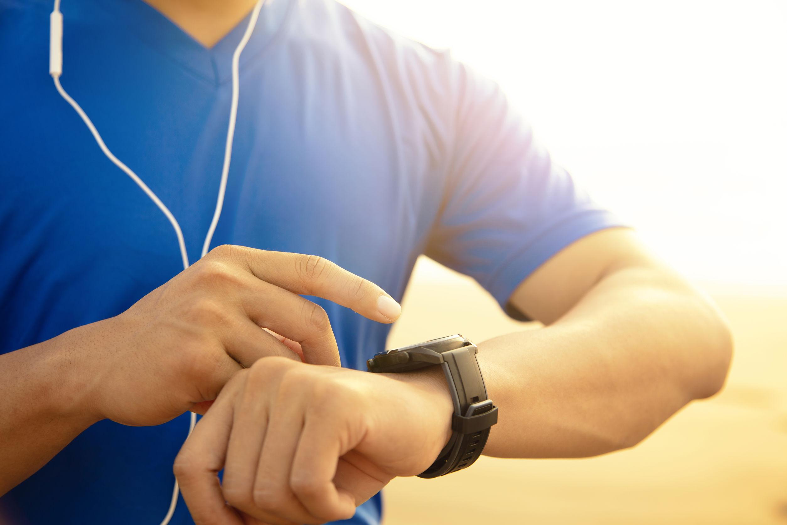 Joven corriendo en la playa y comprobando el monitor de frecuencia cardíaca en el reloj