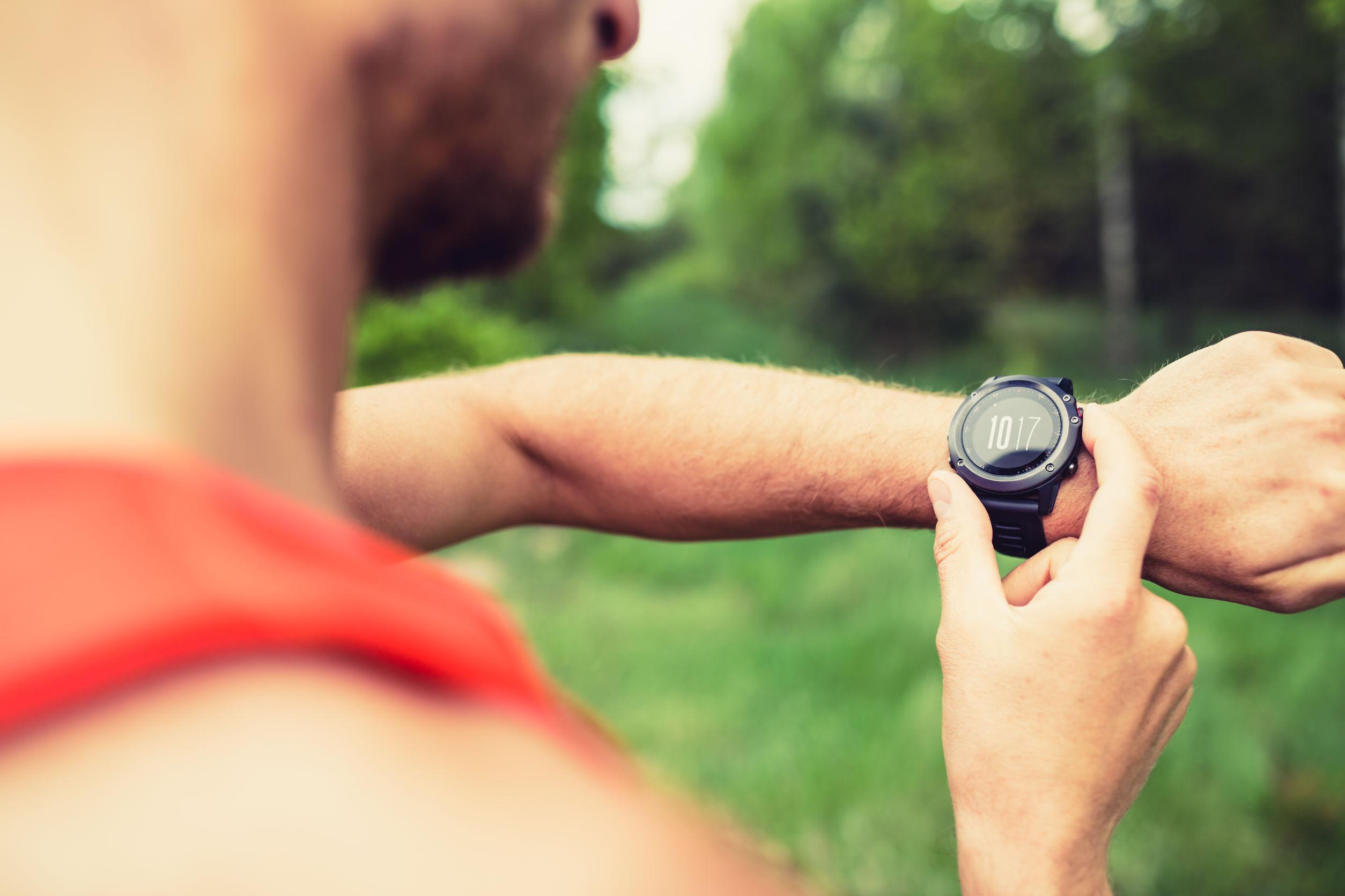 Corredor en pista forestal de montaña comprobar que mira el reloj inteligente