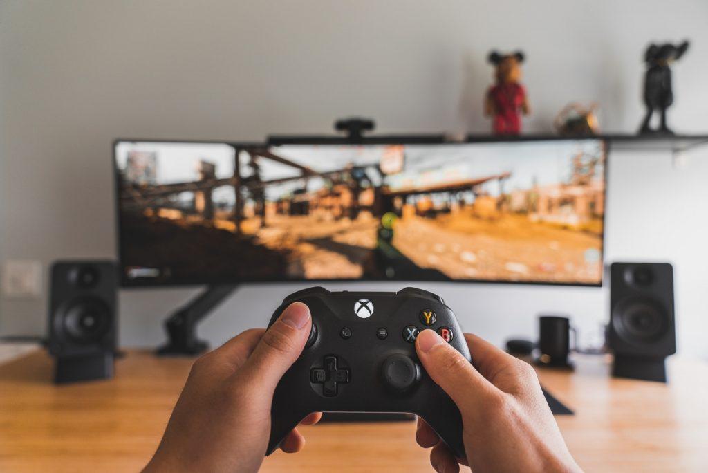 Persona jugando con xbox frente a monitor curvo