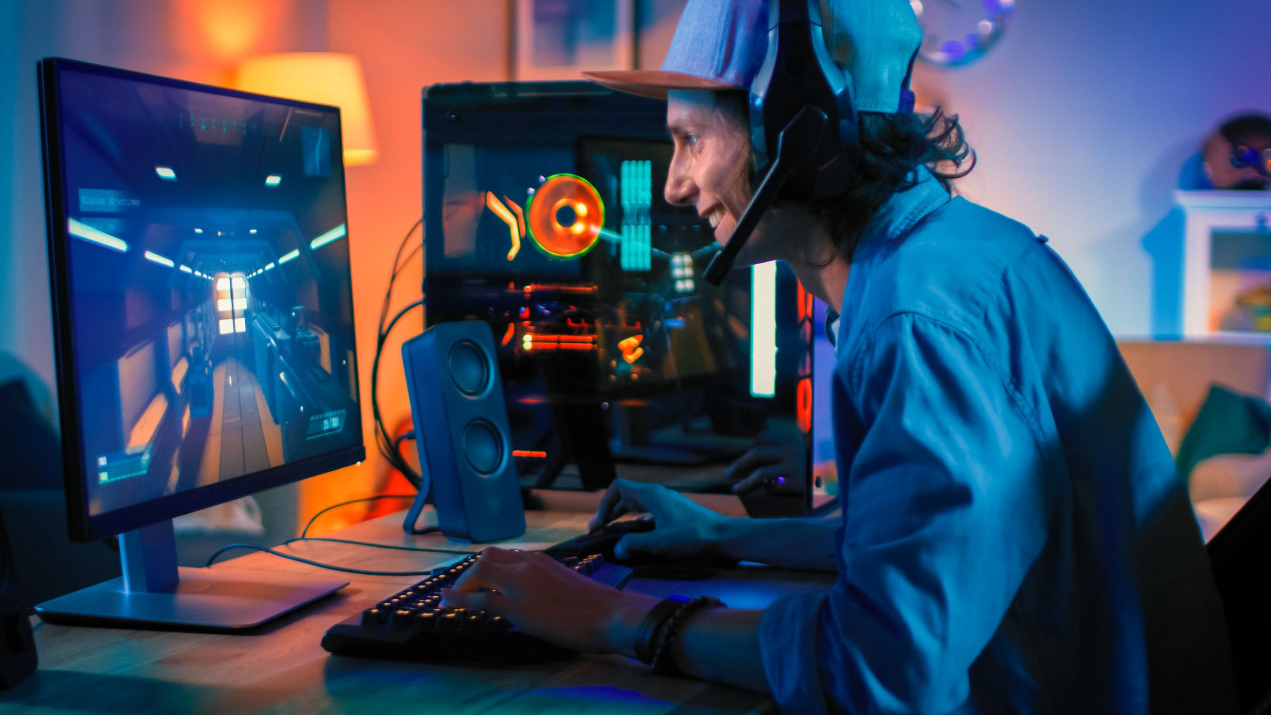 Jugador profesional que juega a un videojuego de disparos en primera persona en línea en su potente computadora personal