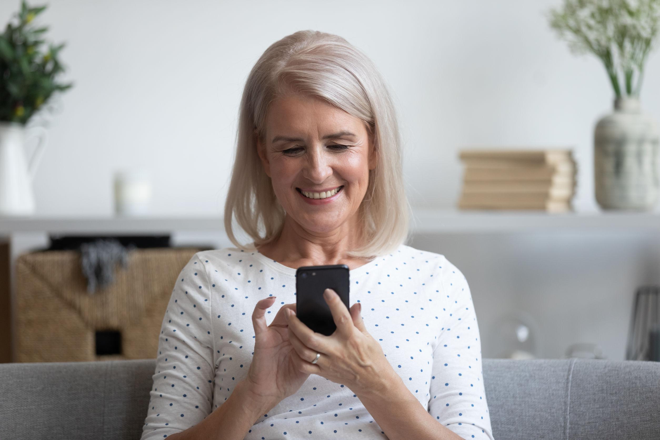 mujer madura sosteniendo el teléfono, usando aplicaciones de dispositivos móviles