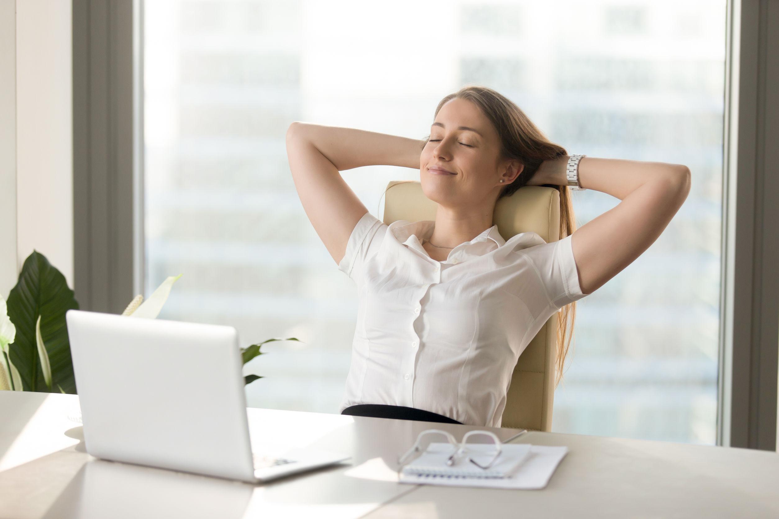 Tranquila, sonriente, empresaria, relajante en una cómoda silla de oficina
