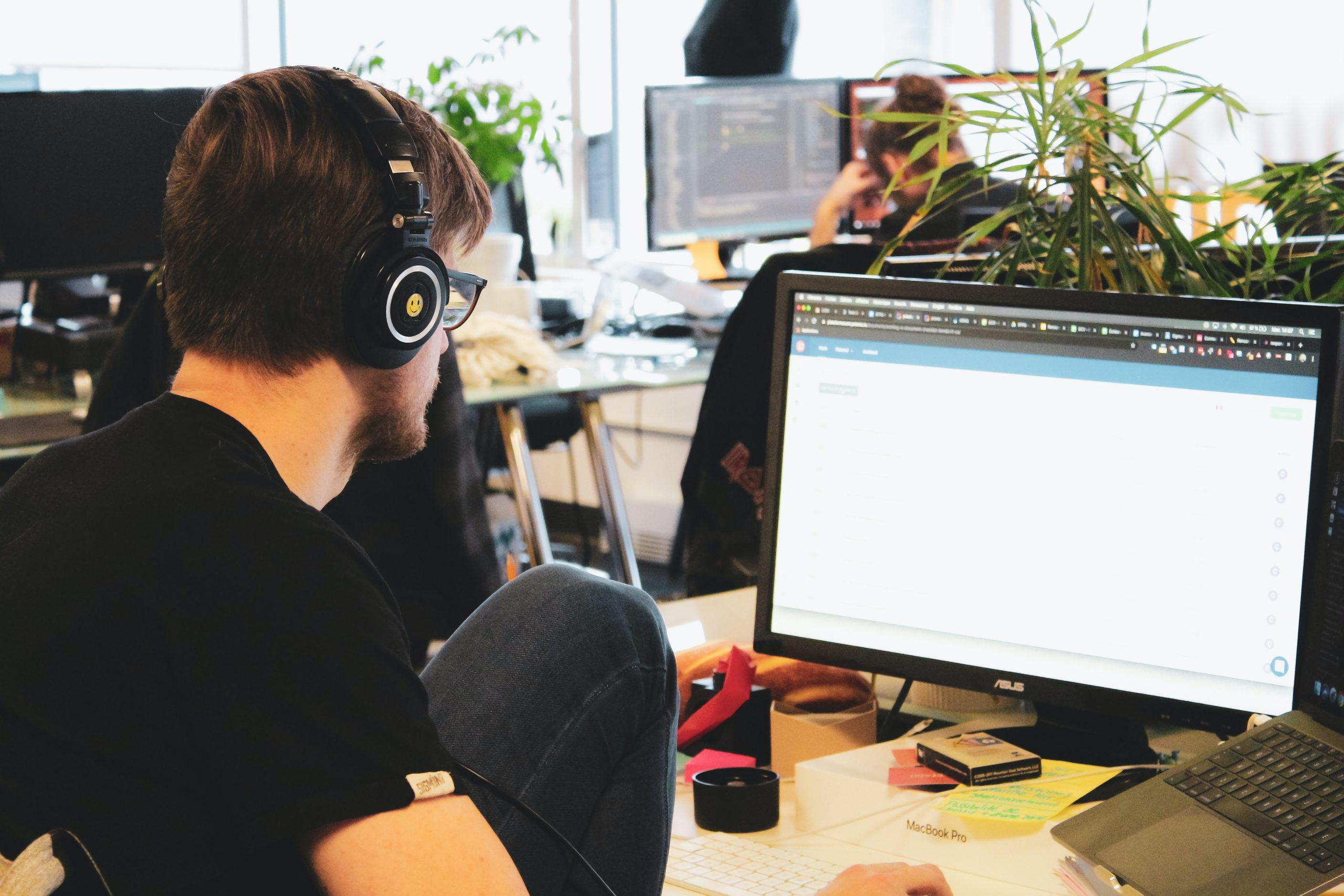 Joven frente a ordenador usando auriculares de diadema